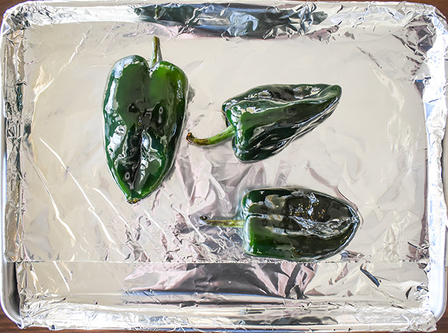 oiled poblano peppers on baking sheet that has been line with foil