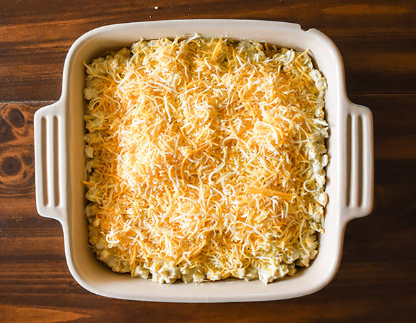 creamy green chili corn bake in baking dish with shredded cheese on top ready to be baked