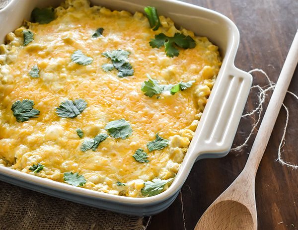 cooked creamy green chile bake in baking dish with wooden spoon beside it