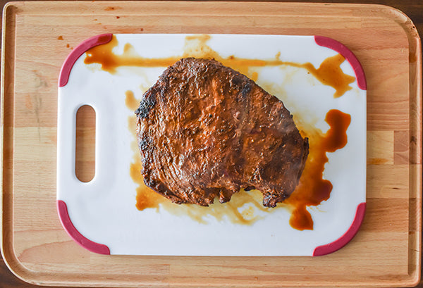 cooked flank steak on cutting board