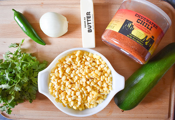 corn, chugwater chili seasoning, zucchini, cilantro, jalapeno, onion, and butter on cutting board