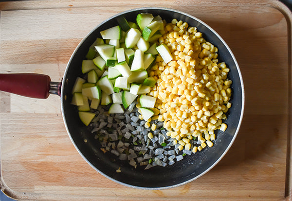 zucchini, corn in skillet with sauteed onion and jalapeno