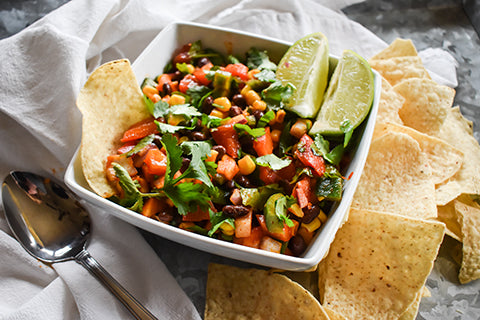 Bowl of cowboy caviar with chips and lime wedges