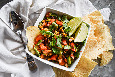 cowboy caviar in bowl with spoon chips and limes