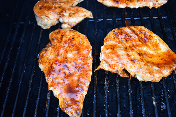 Chugwater Chili red pepper jelly added to chicken breasts on grill