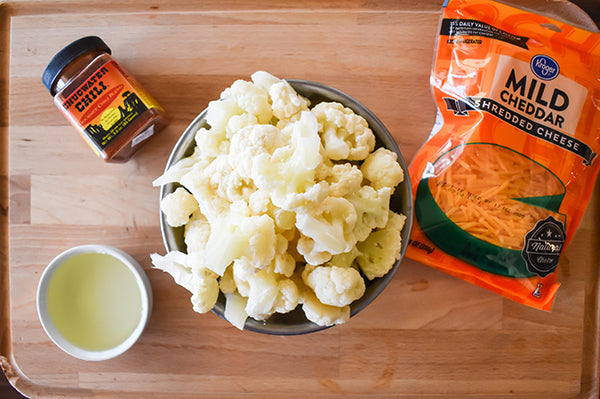 ingredients for chili roasted cauliflower, chugwater chili seasoning, cheddar cheese, cauliflower florets, and olive oil