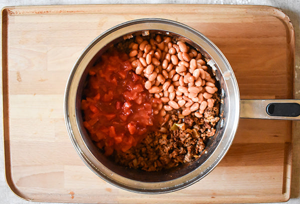 Diced tomatoes, pinto beans, added to chugwater chili seasoned meat in pot