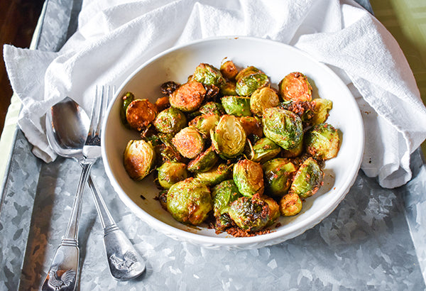 Seasoned Brussel sprouts on plate with spoon and fork