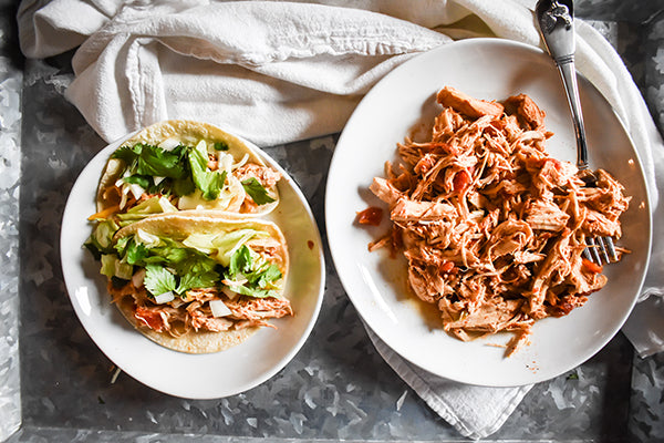 shredded chicken taco meat and tacos on plates