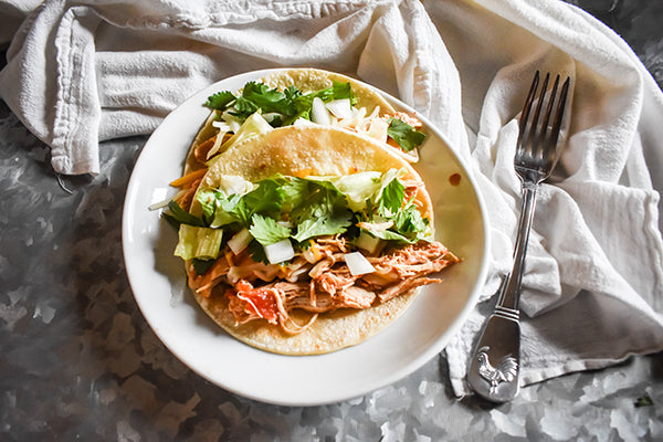 shredded chicken tacos in corn tortillas with lettuce and onion toppings on tray on plate with cilantro and onion