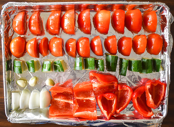 Tomatoes, zuchinni, onion, garlic, and red bell peppers in cookie sheet