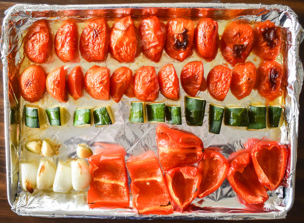 Roasted tomatoes, garlic, red bell peppers, onion, and zucchini on baking sheet