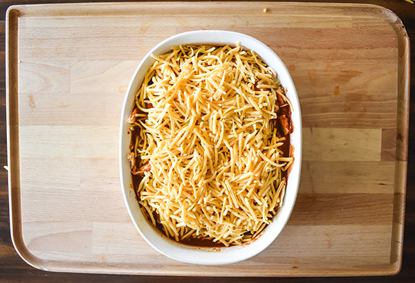 Shredded cheese added on top of the enchiladas
