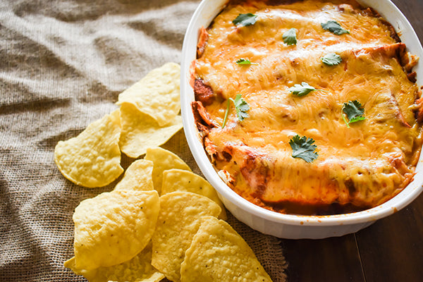 baked enchiladas in pan with tortilla chips beside it