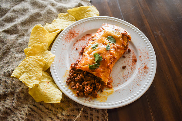 Beef and bean enchilada on plate with tortilla chips next to it