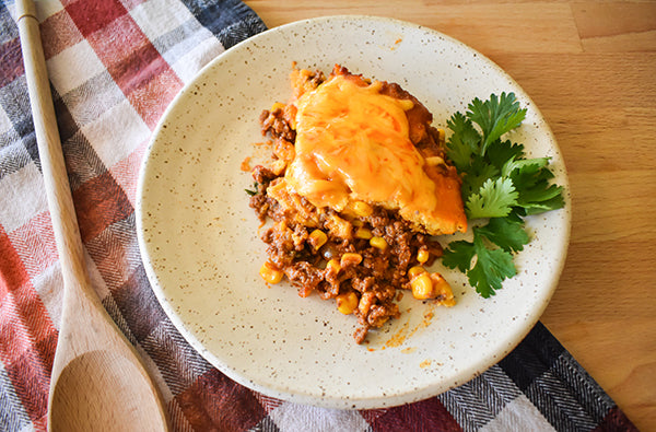 square of tamale pie on plate with spoon and cilantro garnish