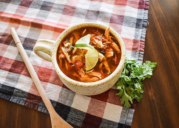 bowl of chili lime chicken soup with lime wedge, cilantro on side and wooden spoon