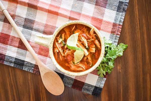 chili lime chicken soup in bowl with wooden spoon and cilantro on side and lime wedge in bowl