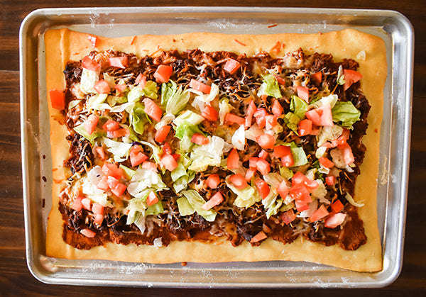 diced tomatoes and lettuce added to top of baked taco pizza