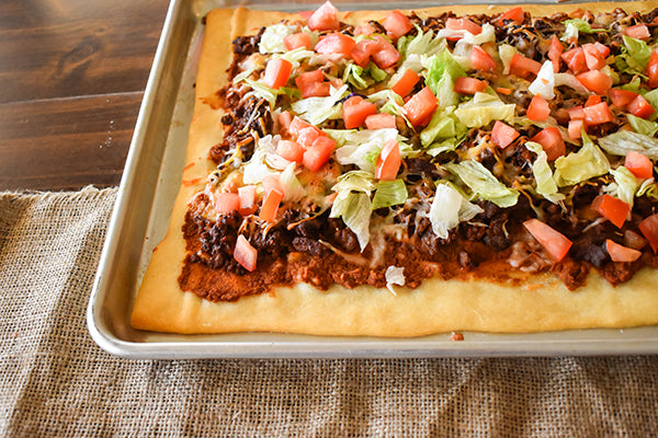 Taco Pizza with diced tomatoes and lettuce on top