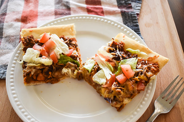 taco pizza ready to eat on plate with a fork