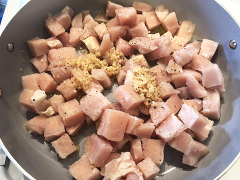 photo of diced chicken breast in pan with garlic