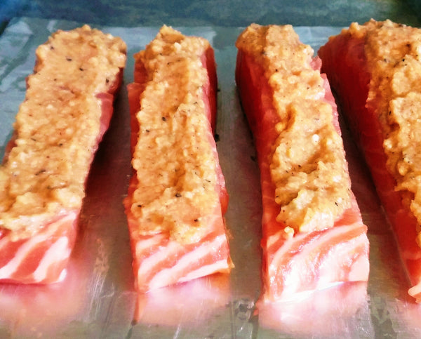 up close photo of salmon covered with buttery topping