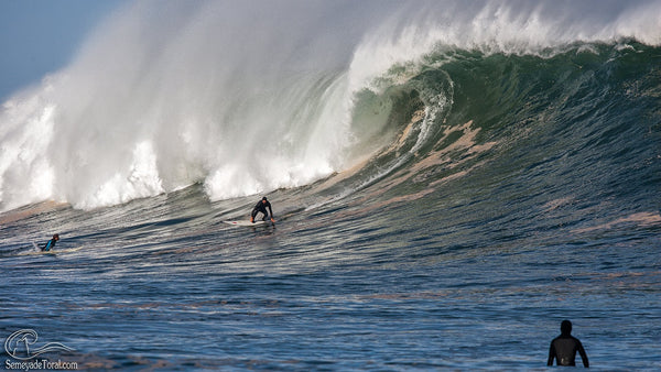 Surfer riding massive wave