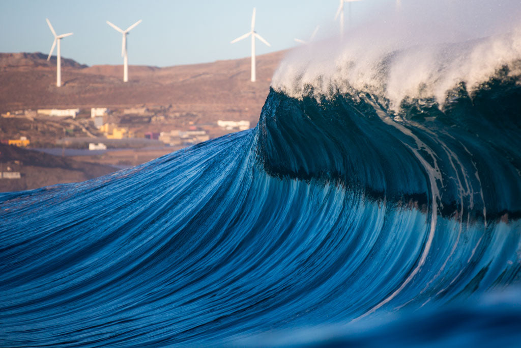Wave breaking with wind turbines in the distance