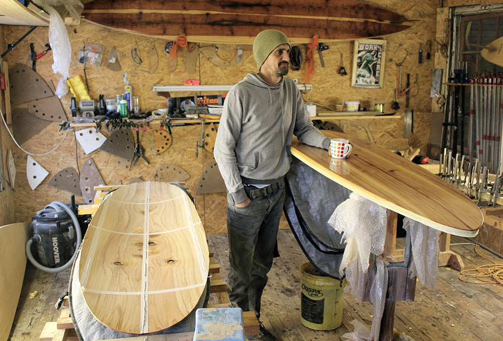 Sealand Gear Ambassador Patrick Burnett Standing Next to wooden surfboard