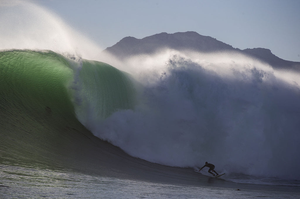 Mike surfing a massive wave in Kommetjie