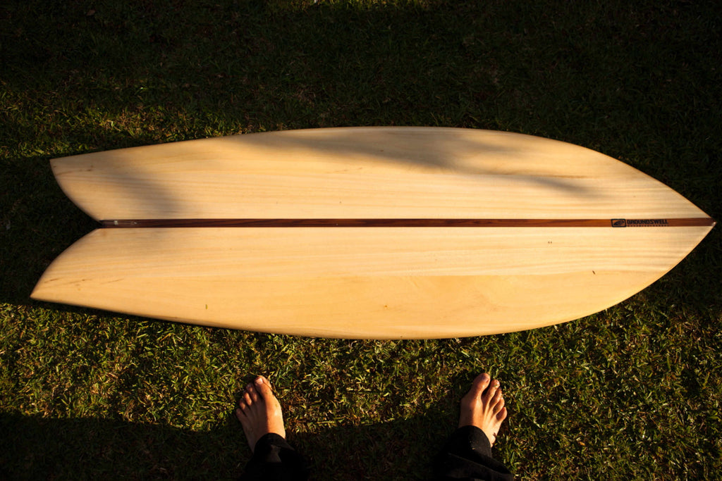 Wooden surfboard lying on the grass