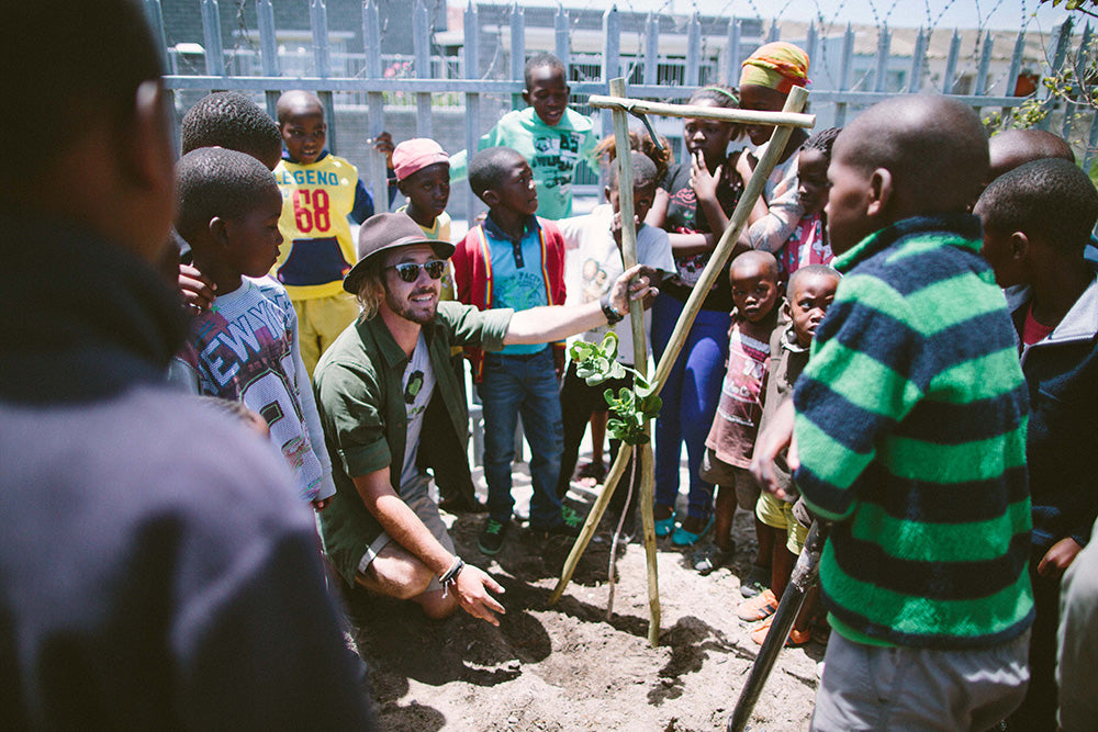 Sealand Gear Ambassador Jeremy Loops showing children how to plant a tree
