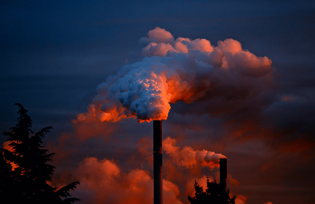 smoke coming out of an industrial chimney at sunset