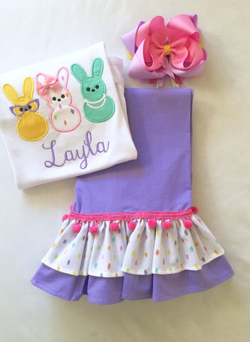 Girls easter outfit with shirt and ruffled pants and easter bow. Shirt embroidered with three decorated bunnies inspired by Peeps! Lavender double ruffle pants finished with a confetti top ruffle and pink pom pom.