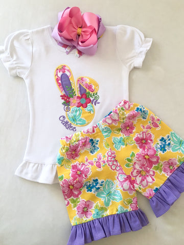 Girls easter outfit with shirt and Single ruffled shorts and easter bow. Shirt embroidered with custom bunny in gorgeous yellow floral and full name monogram in purple! Matching floral ruffled shorties.