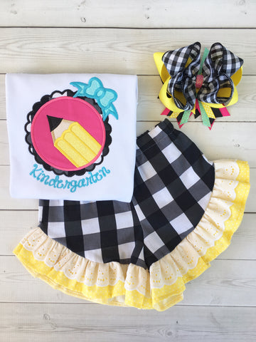 Back to school outfit for girls, embroidered back to school shirt with glitter accents and personalized school year. Yellow pencil in pink fram surrounded by black and white plaid. Black and white plaid shorts with yellow and white lace double ruffle.