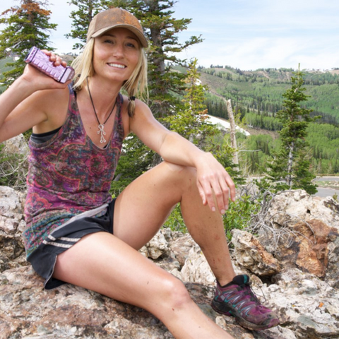 girl holding pepper spray device while sitting on rock in mountains with trees in background