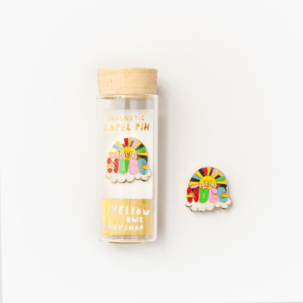 "22k gold gilded enamel ""Hugs"" magnetic lapel pin packaged in a glass vial with cork"