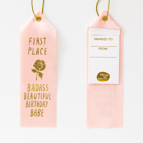 "Light pink satin award ribbon with a gold foil design of a rose with text ""First Place Bada$$ Beautiful Birthday Babe"""