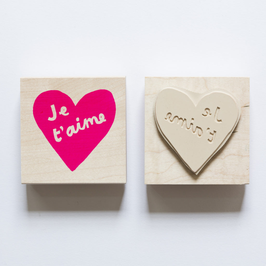 "Wood mounted rubber stamp of a heart and the words ""Je T'aime"""