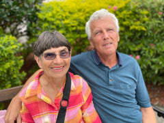 photo of Jim, blind volunteer sitting on a bench with his wife Jean at Aurora Ministries.