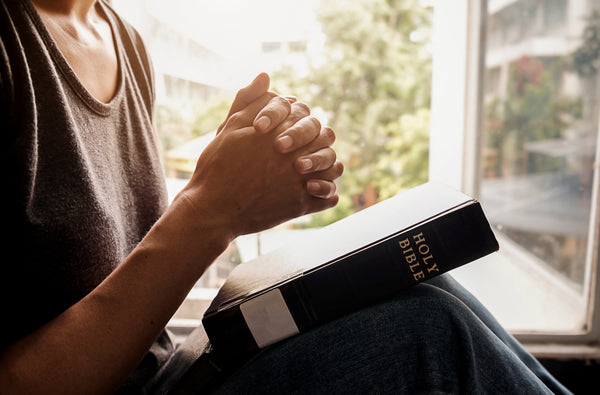 picture of woman sitting by window with a bible praying to God