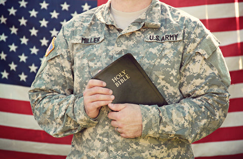 photo of army veteran holding a Bible standing in front of the American flag.