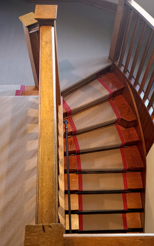 Wooden bannister and the striking red lines of the wool herringbone stair runner.