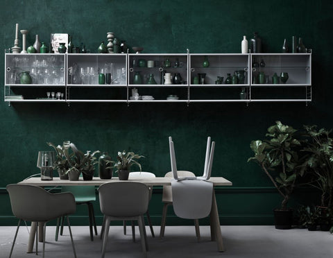 String furniture in a dark green dining room setting