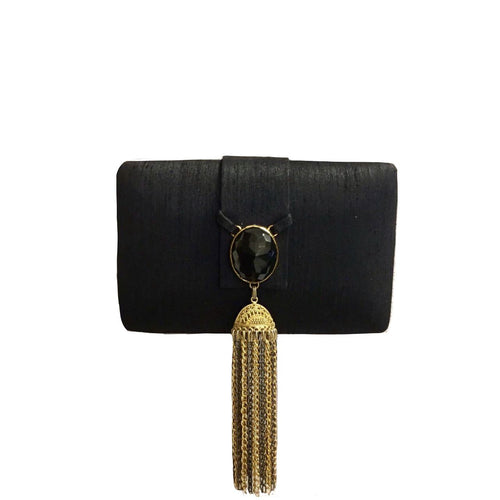 Black box clutch with a black brooch and black & gold hanging tassels