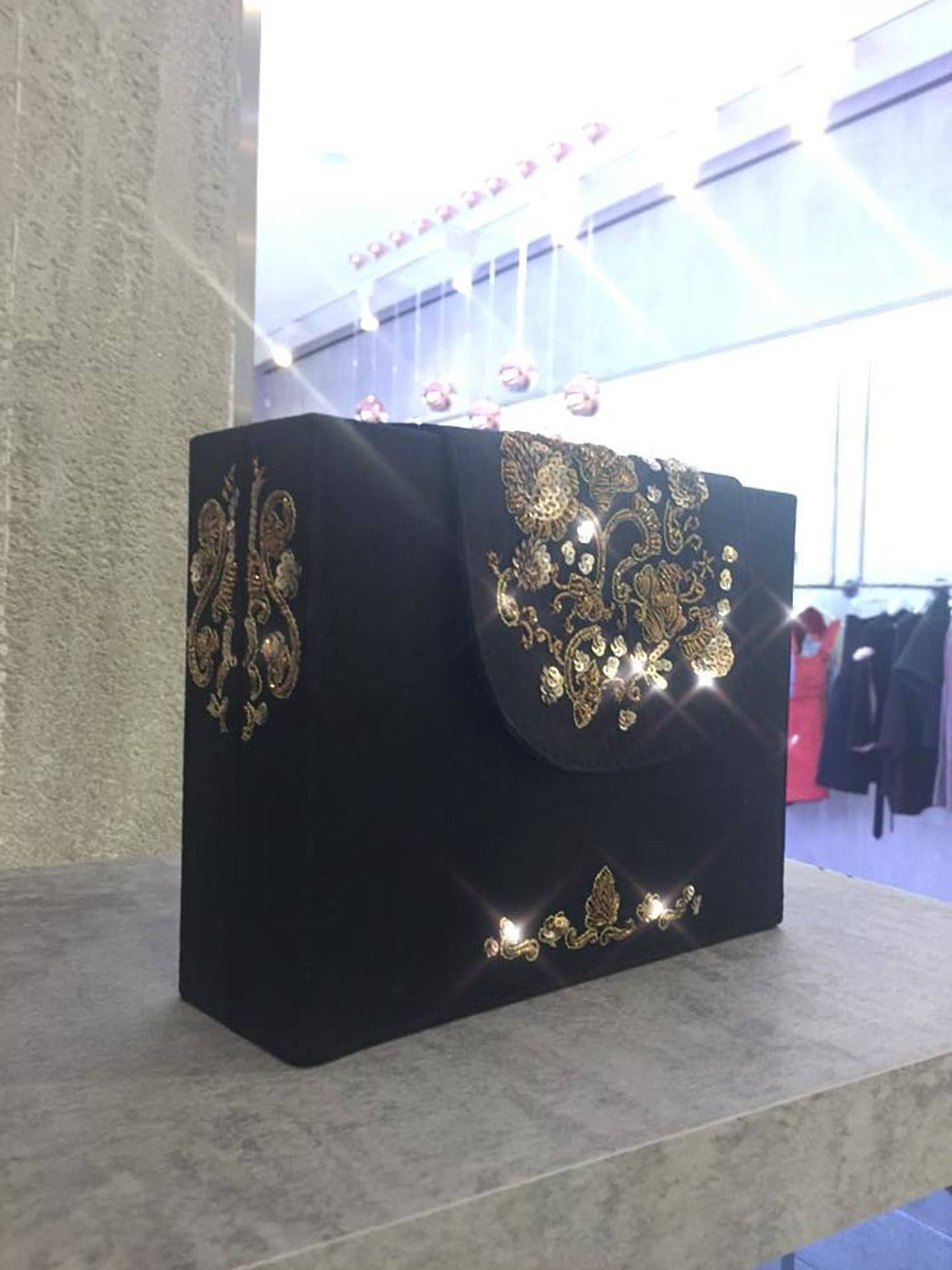 Raw silk fabric with metal and sequin embroidery on flap, sides and the bottom edge Lush black velvet interior lining Magnetic closure on flap