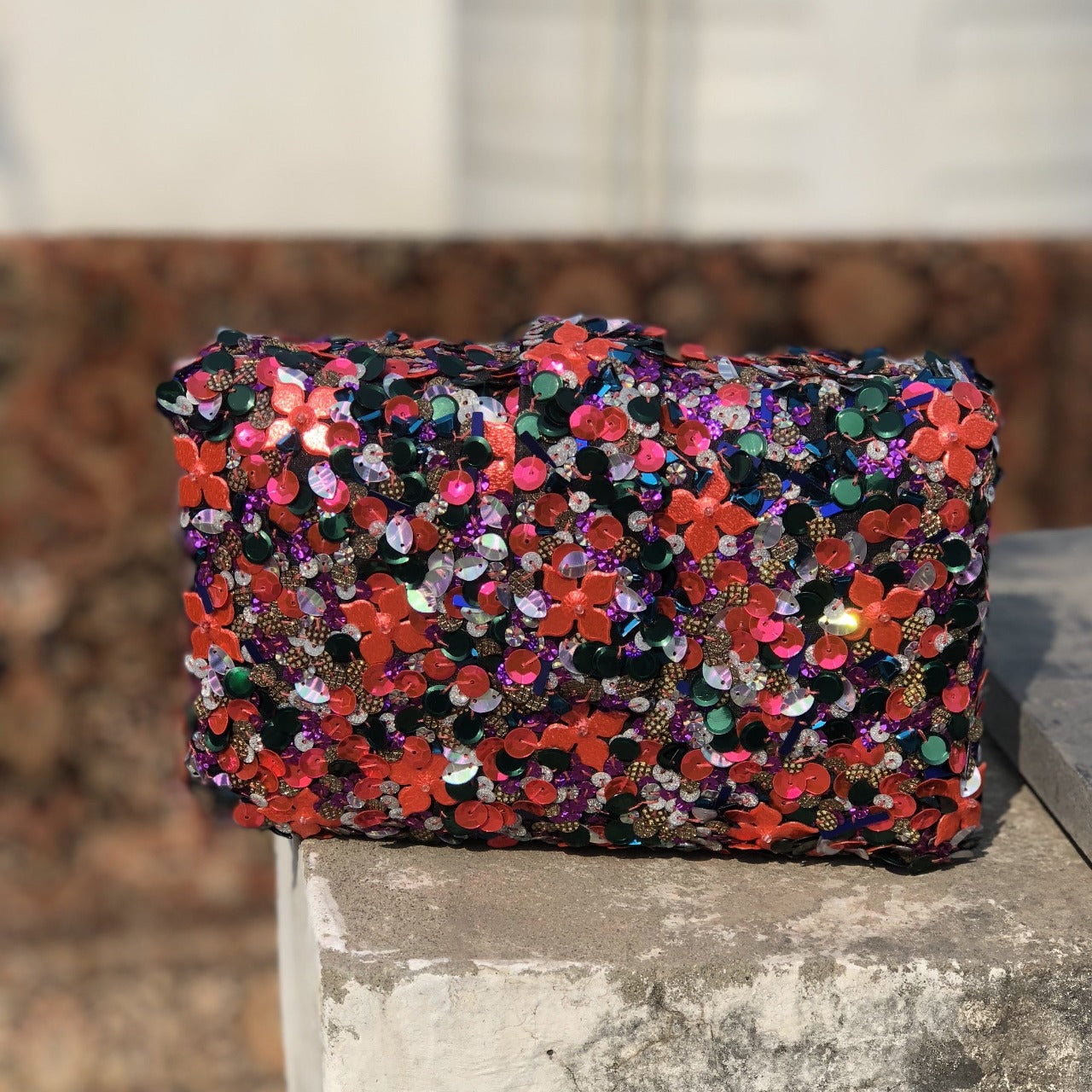 Sequin hand embroidered clutch with a magnetic belt flap as closure, lush velvet lining and a metal chain as handle