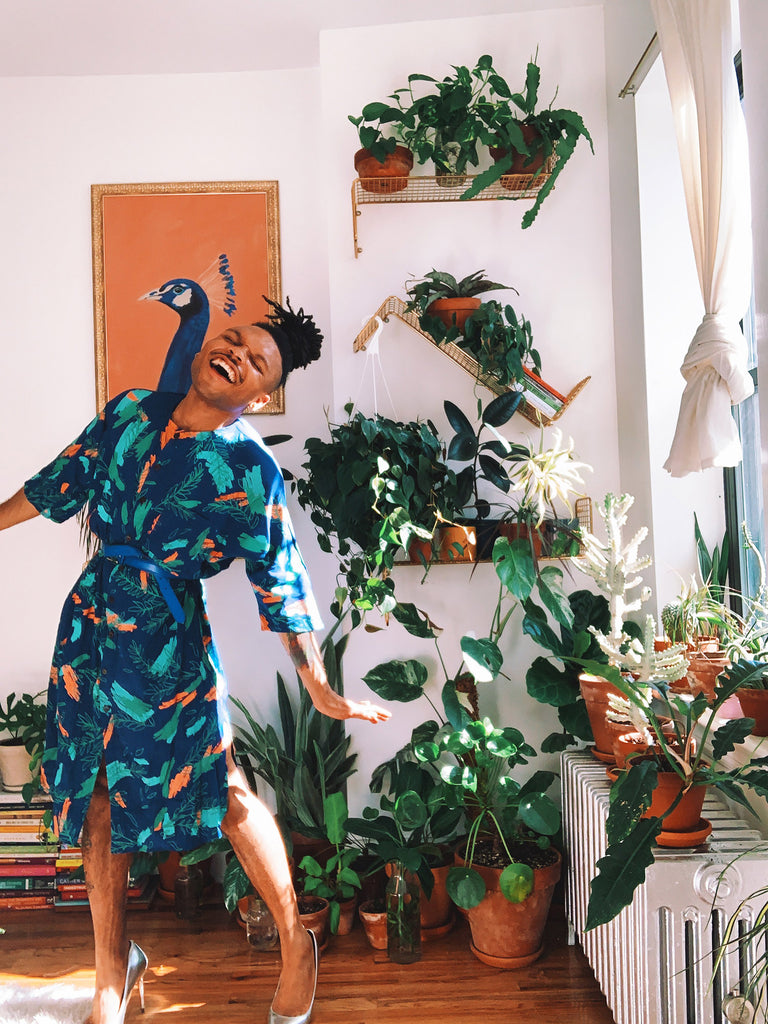 Christopher AKA The Plant Kween wears a royal blue tunic dress with a colorful orange and green botanical print